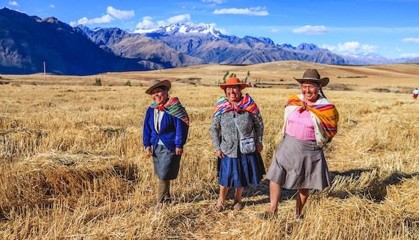 Peruanske kvinner iført fargerike klær i vakre omgivelser