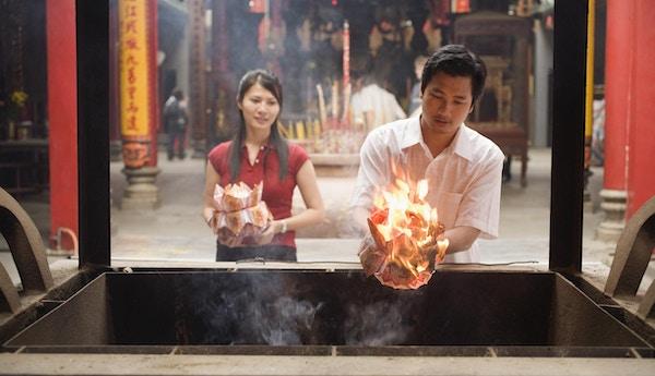Par som tilbyr papirlotter i templet, Vietnam