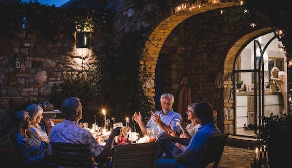 En gruppe voksne venner sitter rundt et utendørs spisebord og spiser og drikker. De snakker alle lykkelig og gleder seg over hverandres selskap når mørket faller på. Bildet er tatt i Toscana, Italia.