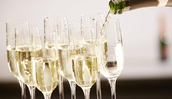 Champagnedrinker som helles på et brett