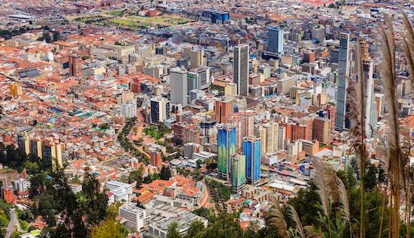 Bogota, Colombia - Et syn ned på sentrum av den andinske hovedstaden Bogota, Colombia i Sør-Amerika, fra fjellet som heter Monserrate. Betongtårn, kirker, plazas, veier og gater kan alle ses. De røde terrakotta takbelagte bygningene til venstre i bildet ligger i La Candelaria, som er den eldste og historiske delen av byen. Området har mange bygninger i den kolonialske, spanske arkitekturstilen. Til høyre er de moderne tårnene i byen. Gaten kalt Las Aguas fremkommer tydelig. Bildet viser det gamle og det nye, i betydelig kontrast. Byen, som ligger på over 8500 fot over gjennomsnittlig havnivå, er det en av de største byene i Latin-Amerika. Fotografi tatt i morgensollys. Horisontalt format.