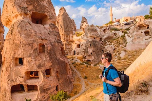 Turist som går langs grottesteiner i Cappadocia, en historisk region i Sentrale Anatolia, Tyrkia