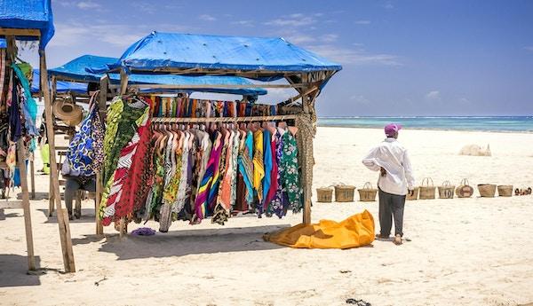 Afrikansk mann og typisk trestativ med fargerike stoffer på Diani Beach, Kenya.
