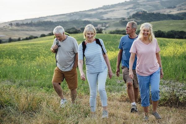 Eldre par som går på det italienske landskapet. Bære ryggsekker og glad. Full lengde, foran.
