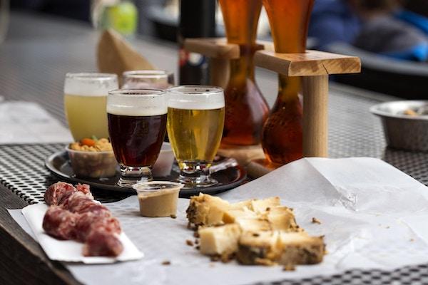 Ulike typer øl som kokosnøtt og kirsebærøl og ost med pølse i restaurant.
