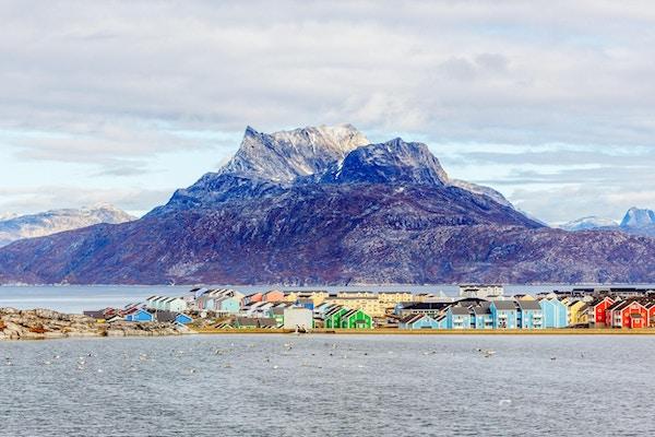 Fargerike Inuit-bygninger i boligområdet i Nuuk by med innsjø i forgrunnen og snøtoppen på fjellet Sermitsiaq, Grønland