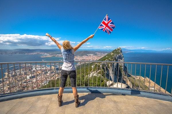 Kvinne med det britiske flagget i hånden på toppen av Gibraltar Rock. Gibraltar er et territorium i Sør-Vest-Europa som er en del av Storbritannia.