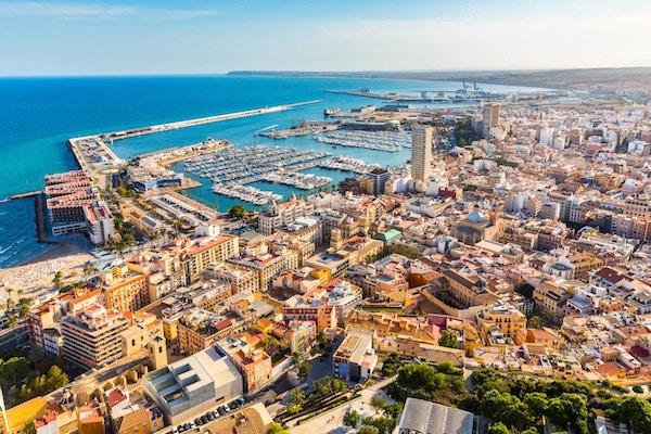 Panoramautsikt over Alicante med sjø, havn og hus.