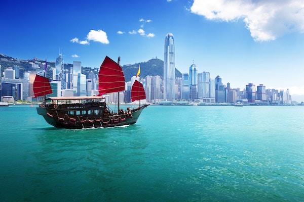 Hongkongs skyline fra havnen på dagtid. Vannet er blågrønt, og et tradisjonelt kinesisk søppelskip med firkantede røde seil ligger i vannet i forgrunnen. Bygningene i horisonten er av ulik høyd og for det meste hvite foran en åsside dekket av mindre bygninger under en blå himmel.