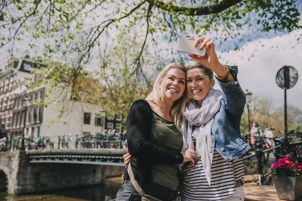 To kvinner i Amsterdam som tar en selfie ved elven.