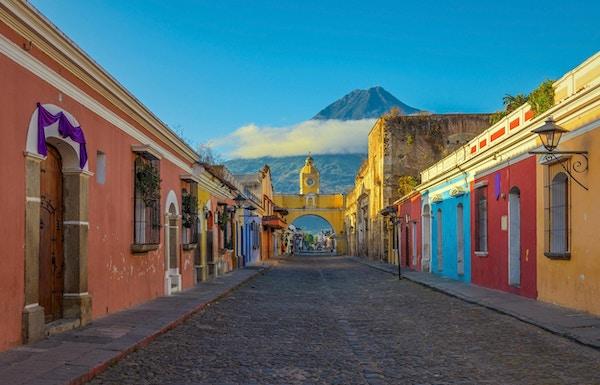 Den historiske byen Antigua ved soloppgang med utsikt over hovedgaten og Catalina-buen og vulkanen Agua i bakgrunnen, Guatemala.