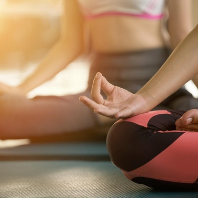 Nærbilde hender av kvinne som gjør yoga og utøver meditasjon.