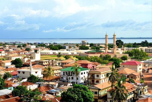 Banjul, Gambia: skyline av den lave bygningen i Gambia med elven Gambia som bakgrunn - minareter av kong Fahad-moskeen til høyre