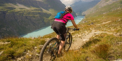 En dame med en rosa T-skjorte som sykler på terrengsykkel langs en løype over en blå innsjø i de sveitsiske alpene.