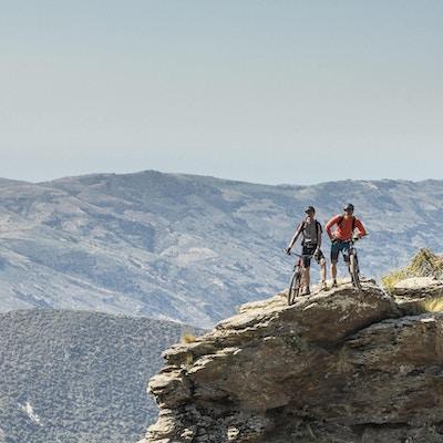 To mannlige terrengsyklister poserer på en naturskjønn klippe i den andalusiske Sierra Nevada, som er en fjellkjede i provinsen Granada og, litt lenger, Málaga og Almera i Spania. Det inneholder det høyeste punktet på det kontinentale Spania og det tredje høyeste i Europa etter Kaukasus-fjellene og Alpene, Mulhacén på 3447 meter over havet. Det er et populært turistmål. Deler av serien er inkludert i Sierra Nevada nasjonalpark. Området er også blitt erklært som et biosfæreservat. Canon EOS 5D Mark IV, 1/160, f / 11, 105 mm.
