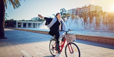 En ung kvinne som sykler i parken uten hender på rattet