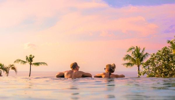 Romantisk kjærestepar som ser på en vakker solnedgang fra et svømmebasseng