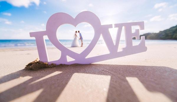 """Skilt - """"kjærlighet"""" på sandstranden med par inne i hjertet."""