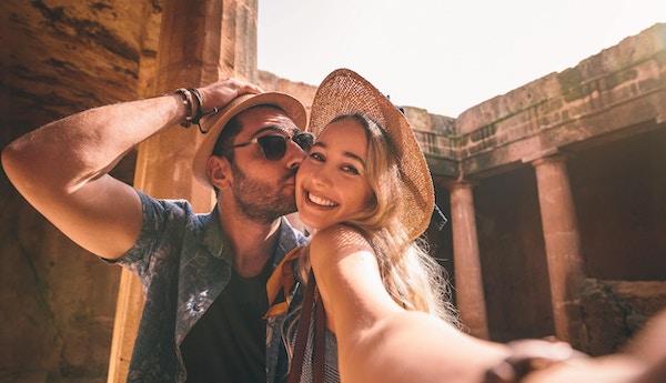 Par tar selfies mens de gjør sightseeing ved eldgammelt monument med steinsøyler i Europa.