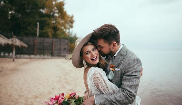 lykkelig brud og brudgom i boho stil omfavnelse på stranden
