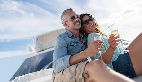 Portrett av et kjærlig par som seiler på en yacht og drikker champagne mens de nyter sommeren