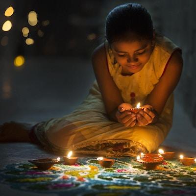 En jente som lager Rangoli og dekorerer med oljelys under Divali-feiringen i India.