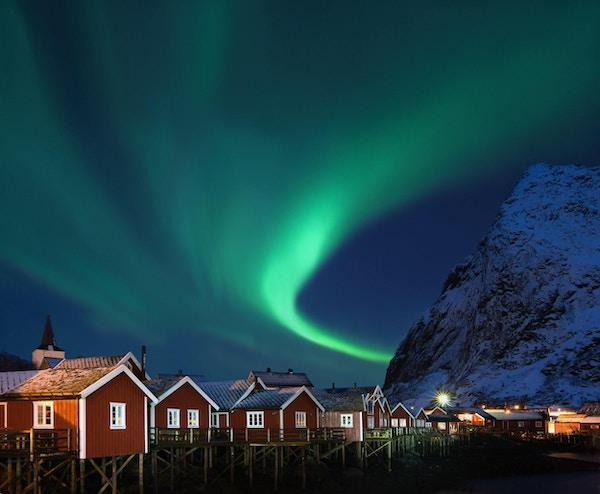 Nydelig form på nordlys (Aurora borealis) over tradisjonelle norske fiskehytter (rorbuer) og snøhvit fjell.