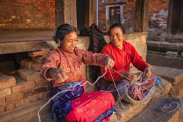 To nepalske kvinner som spinner ull foran hjemmet sitt i Bhaktapur, Kathmandudalen i Nepal.