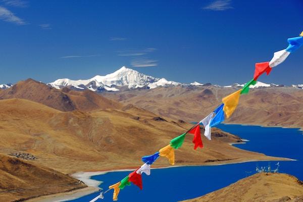 Bønneflagg på Kamba La- passet med utsyn med den turkisfargede Yamdrok Tso-Upper-sjøen og det 7206 meter høye fjellet Nojin Kangsang.