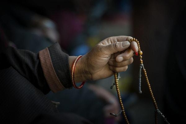 Hendene til en tibetansk buddhist som beveger seg gjennom bønneperlene mens han synger.