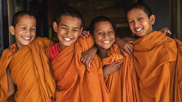 Gruppe av glade nybegynner-buddhistiske munker i dører i klosteret i Bhaktapur, Nepal. Bhaktapur er en gammel by i Kathmandu-dalen og er oppført som et verdensarvsted av UNESCO for sin rike kultur, templer og kunstverk av tre, metall og stein.