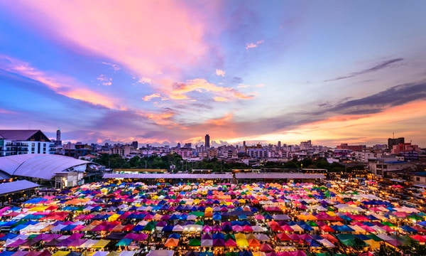Solnedgang, byutsikt og fargerikt marked i Thailand.
