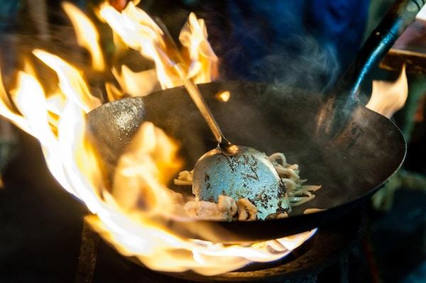 Nudler tilberedt i en Wok på åpen ild på en Street food-restaurant på Yaowarat Road, Bangkok, Thailand.