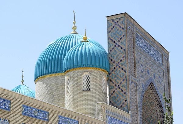 En del av inngangen til moskeen med turkise kupler og en minaret i Tashkent, Usbekistan.