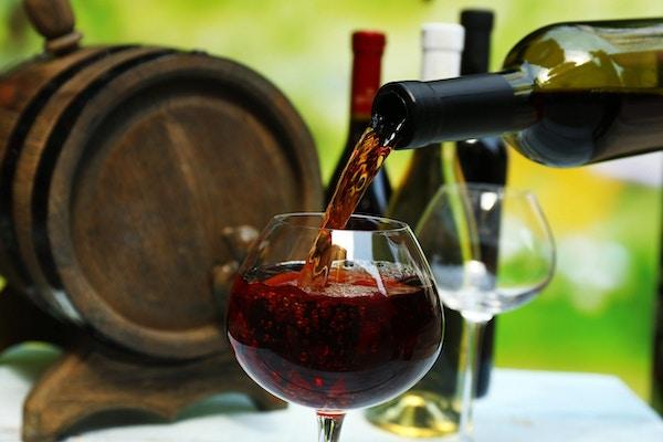 Rødvin som helles i vinglass, nærbilde