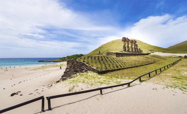 Syv av de berømte steinstatuene på Påskeøya som står på rekke ved sandstranden