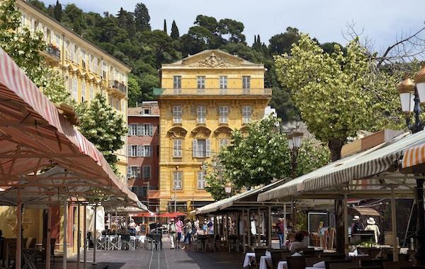 Gammel bygning og en kafé i Cours Saleya. Cours Saleya er et sted med utendørsrestauranter, butikker og et marked. Folk går på gaten, Nice.