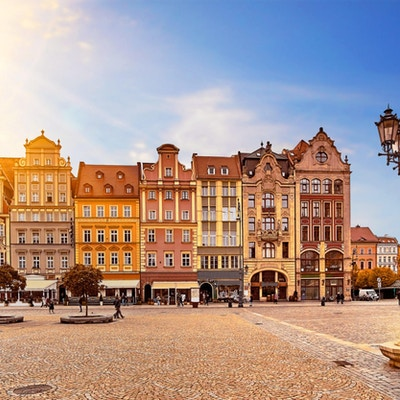 Sentrale markedstorg i Wroclaw Polen med gamle fargerike hus, gatelyslykt og vandrende turistpersoner ved nydelig fantastisk soloppgang om morgenens soloppgang. Reiseferiekonsept.