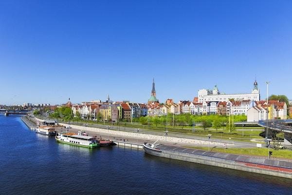 Stor elvepram og sightseeingskip fortøyd til vollen på elven Odra med gamlebyen i Szczecin i bakgrunnen