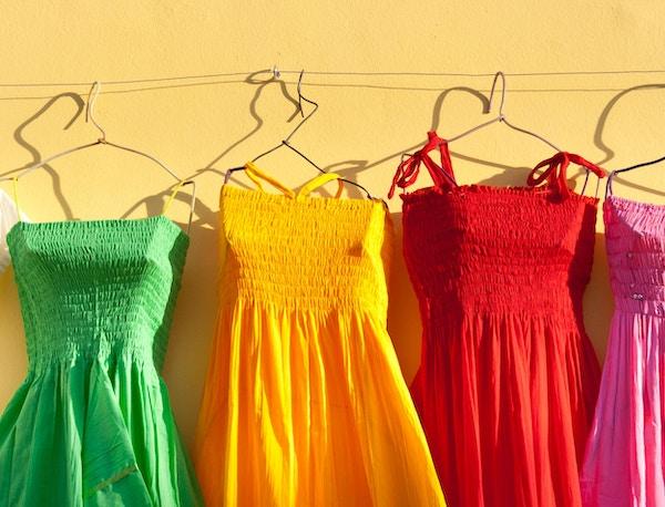 Fargerike meksikanske kjoler vist på kleshengere i en turist-souvenirbutikk i Cozumel, Riviera Maya, i Cancun Mexico. Den fargerike latinermoten er en populær turist-suvenir. Fotografert på Plaza del Sol på øya Cozumel i horisontalt format.