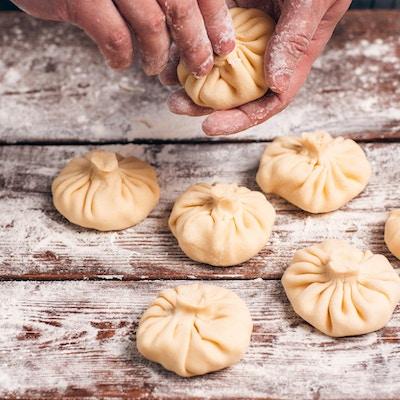 Håndlaget matlaging av khinkali på kjøkkenet. Cook tilbereder nasjonalt georgisk måltid med deig og kjøtt, tilberedningsprosess. Tradisjonell mat, kjøkkenkonsept