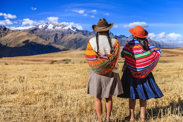 Peruvianske kvinner i nasjonale klesdrakter ved foten av Andesfjellene.