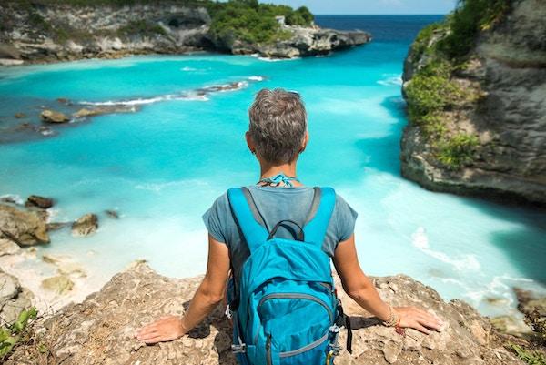 ryggsekk reisende kvinne sitter i nærheten av sjø stup, utsikt over havet og den blå bukten lagunen