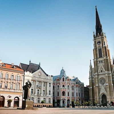 """""""Det sentrale torget i Novi Sad, Serbia eller Trg Slobode. Synlig er tradisjonell arkitektur, parochial romersk-katolske kirke med navnet Marias og statuen av Svetozar Miletic. Se flere bilder som dette i:"""""""