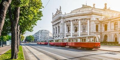 Den berømte Wiener Ringstrasse med det historiske Burgteateret (Imperial Court Theatre) og en tradisjonell rød, elektrisk trikk i soloppgang sett med retro vintage filtereffekt i Wien, Østerrike.
