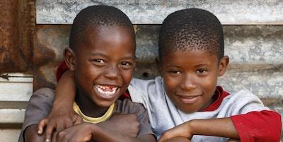 To unge afrikanske gutter som satt foran sin ydmyke hytte, rett utenfor Johannesburg, Sør-Afrika.
