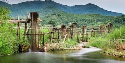 Vanningssystem bestående av vannhjul i tre med elv og frodige fjell. Foto.