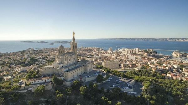 Høydevinkelsikt av bybildet ved sjøen. Notre Dame de la Garde i Marseille mot klar himmel. Bygninger ved sjølandskap på solrik dag.