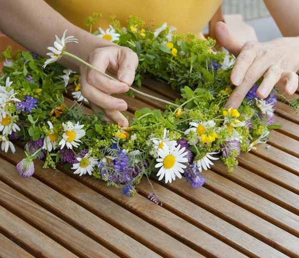 Hender som lager en blomsterkrans av ville blomster til sommerdekkedekorasjon.