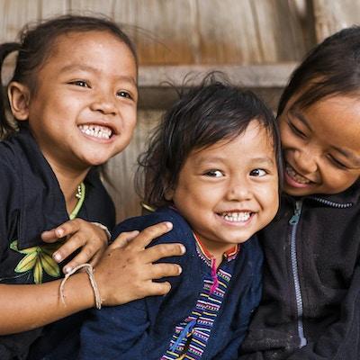 Tre små jenter som har det gøy i landsbyen i Nord-Laos.